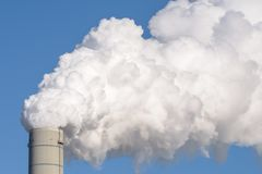 A smokestack of a coal power plant. Close up of a smokestack of a fossil fuel coal power plant with white smoke against a completely blue sky and lots of copy Stock Images