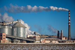 A Smokestack Emits Smoke - The Clear Blue Sky In The Background stock image
