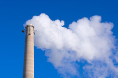 Smokestack and Gas Emissions Against Blue Sky. Industrial chimney or smokestack emitting gases visible against blue sky Stock Images