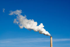 Smokestack and horizontal white smoke on blue sky. Industrial smokestack spewing white polluting smoke cloud horizontally from right to left into clear blue sky Royalty Free Stock Image