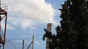 Smokestack of industrial building behind tree stock footage