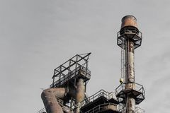 Smokestack with ladders and catwalks against a grey sky, steel mill. Horizontal aspect stock image
