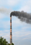 Smokestack polluting the environment vertical. Smokestack polluting the environment. dark gray smoke on the background of the cloudy sky. vertical image Stock Images