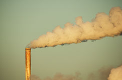 Smokestack And Smoke. Old rusty smokestack with plume of smoke lit by early morning light Royalty Free Stock Photography
