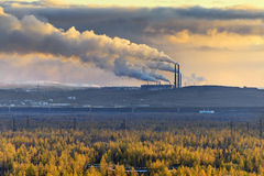 Smokestack smokestacks that pollute the atmosphere. Ecological catastrophy. Polar tundra, deep autumn. Sunset, bad lighting conditions Royalty Free Stock Photos