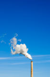 Smokestack and vertical white smoke on blue sky. Industrial smokestack spewing white polluting smoke cloud vertically up and left into clear blue sky Royalty Free Stock Images