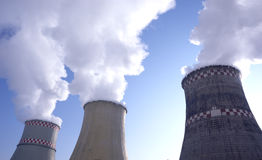 Smokestacks. Of thermal power plant with steam on blue sky background Stock Photos