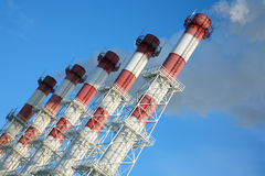 Smokestacks against blue sky. Stock Photo