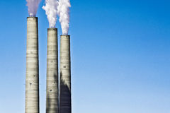 Smokestacks of a Coal Plant Polluting Concept against Clear Blue Royalty Free Stock Photo