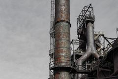 Smokestacks, ladders,and walkways of steel mill against gray sky, copy space. Horizontal aspect stock photo