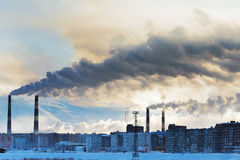 Smokestacks polluting the air over the city. Winter landscape stock photography