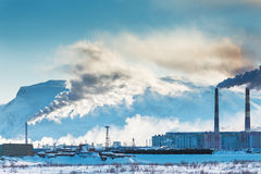 Smokestacks polluting the air over the city. Winter landscape royalty free stock images