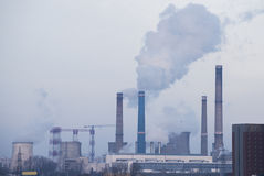 Smokestacks polluting. The city in a winter day royalty free stock photo