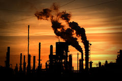 Smokestacks Polluting Environment. Smokestacks blowing smoke into the atmosphere at sunset stock images