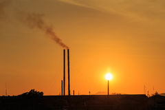 Smokestacks at sunset time. Silhouette of Smokestacks at sunset time stock photo