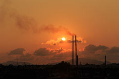 Smokestacks at sunset time. Silhouette of Smokestacks at sunset time in Phuket, Thailand royalty free stock images