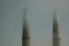 Smokestacls nella nebbia Fotografie Stock