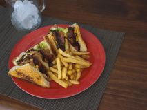 Smokey BBQ Chicken Club Sandwich with French Fries. Served on a red plate, with a modern texture tablecloth on a wooden table stock photography