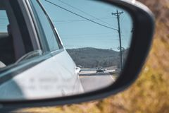 Smokey berg till och med en bakre veiwbilspegel royaltyfri foto