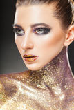 Smokey eyes. Portrait of a young woman with makeup fashion on a dark background. Smokey eyes. Lips and neck are covered with sparkles Stock Image