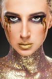 Smokey eyes. Portrait of a young woman with makeup fashion. Smokey eyes. Lips and neck are covered with sparkles Royalty Free Stock Photo