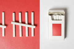 About Smoking. Pack of Cigarettes on white and some cigarettes on red paper background Stock Image