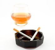 Smoking. Cigarettes and alcohol in the ashtray, over white background Royalty Free Stock Photos