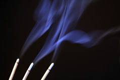 Smoking. Three smoking incense sticks on black background stock images