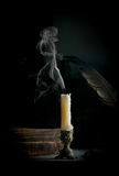 Smoking above the candle standing on the table with old burned b Royalty Free Stock Images