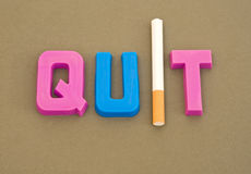 Smoking advice: quit !. A closeup image of the word quit in colorful upper case letters with the letter 'I' replaced by a filter tipped cigarette Royalty Free Stock Image