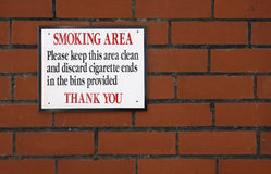 Smoking area sign. On a brick wall royalty free stock photo