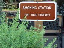 Smoking Area Sign. Sign in a park announcing that smoking is permitted in that location. Bench is situated near the sign and the windows of the visitor center Royalty Free Stock Images