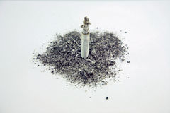 Smoking ashes. A lit smoke standing in a pile of ashes Stock Images