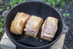 Smoking bacon outdoors. Smoked bacon in the open air. Homemade Cooking Stock Photo