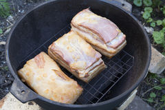 Smoking bacon outdoors. Smoked bacon in the open air. Homemade Cooking Royalty Free Stock Photography