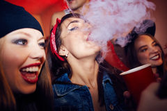 Smoking in bar. Young girl with drink smoking in bar royalty free stock photo