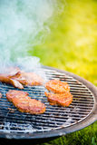 Smoking bbq grilling meat, sunlight Royalty Free Stock Photos