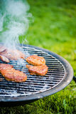 Smoking bbq grilling meat, sunlight Royalty Free Stock Photography