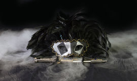 Smoking Black Mask with Dagger. An evil black and silver carnival mask rests on a swirling mass of white smoke with a jeweled knife Royalty Free Stock Photo
