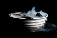 Smoking bowl of lava rocks and spoon Stock Images