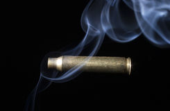Smoking brass from a rifile on black Royalty Free Stock Photo