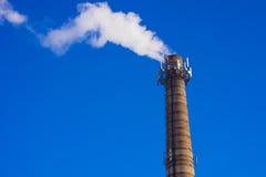 Smoking brick tower with mobile antenna on top Stock Image