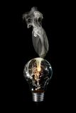 Smoking bulb. Light bulb with burns out with white smoke Stock Image