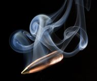 Smoking bullet. Copper bullet with a green polymer tip that is smoking Stock Photos
