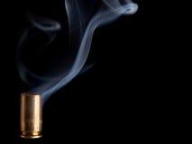 Smoking bullet casing. Smoking 9mm bullet casing over black background royalty free stock photo