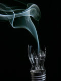 Smoking busted lightbulb. Smashed lightbulb fixture oozing smoke streams Stock Image