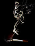 Smoking can cause death. A cigarette wastes away. Its smoke creates the shape of a skull Royalty Free Stock Image