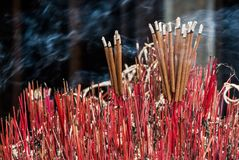 Smoking candles in asian temple. Buddhist altar with multiple red smoking candles abstract background Stock Photography