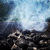 Smoking charcoal. A close up of hot charcoal with dense smoke above it Stock Image