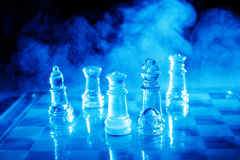 Smoking Chess. Blue light glass chess with some smoke in the background Stock Photos